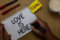 Handwriting text writing Love Is Here. Concept meaning Romantic feeling Lovely emotion Positive Expression Care Joy Man holding ma. Rker notebook clothespin stock photography