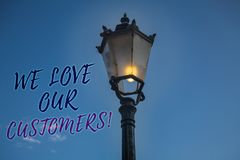Handwriting text writing We Love Our Customers Call. Concept meaning Client deserves good service satisfaction respect Light post. Blue sky enlighten ideas Royalty Free Stock Image