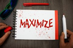 Handwriting text writing Maximize. Concept meaning Increase to the greatest possible amount or degree Make larger Googles glasses. Pen marker cap notepad stock image