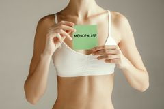 Handwriting text writing Menopause. Concept meaning Cessation of menstruation. Young adult woman holding paper card for sign or symbol. Cut out part of body stock image