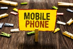 Handwriting text writing Mobile Phone. Concept meaning A handheld device used to send receive calls and messages Clothespin holdin. G yellow paper note several stock photo