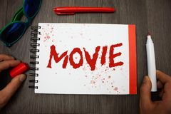Handwriting text writing Movie. Concept meaning Cinema or television film Motion picture Video displayed on screen Googles glasses. Pen marker cap notepad Royalty Free Stock Image