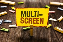 Handwriting text writing Multi Screen. Concept meaning Having or involving several screen especially in a cinema Clothespin holdin. G yellow paper note several royalty free stock photography
