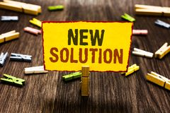 Handwriting text writing New Solution. Concept meaning Modern Innovation Latest effective approach to a problem Clothespin holding. Yellow paper note several royalty free stock images