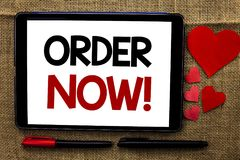 Handwriting text writing Order Now. Concept meaning Buy Purchase Order Deal Sale Promotion Shop Product Register written on Tablet. Handwriting text writing Stock Photo