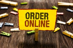 Handwriting text writing Order Online. Concept meaning Buying goods and services from the sellers over the internet Clothespin hol. Ding yellow paper note stock photo