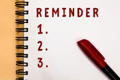 Handwriting text writing Reminder. Concept meaning thing that causes someone to remember something event or date Marker. Over open spiral notebook white page stock images