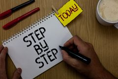 Handwriting text writing Step By Step. Concept meaning Slow progress Road to success Direction development Growth Man holding mark. Er notebook clothespin stock photos