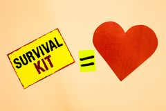 Handwriting text writing Survival Kit. Concept meaning Emergency Equipment Collection of items to help someone Yellow piece paper Royalty Free Stock Photos