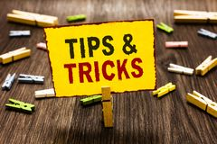 Handwriting text writing Tips and Tricks. Concept meaning Steps Lifehacks Handy advice Recommendations Skills Clothespin holding y. Ellow paper note several royalty free stock image