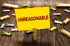 Handwriting text writing Unreasonable. Concept meaning Beyond the limits of acceptability or fairness Inappropriate Clothespin hol. Ding yellow paper note stock photos