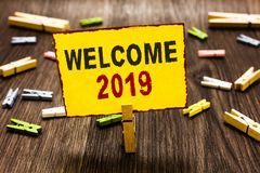 Handwriting text writing Welcome 2019. Concept meaning New Year Celebration Motivation to Start Cheers Congratulations Clothespin. Holding yellow paper note royalty free stock images