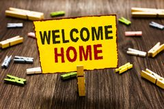 Handwriting text writing Welcome Home. Concept meaning Expression Greetings New Owners Domicile Doormat Entry Clothespin holding y royalty free stock images