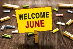 Handwriting text writing Welcome June. Concept meaning Calendar Sixth Month Second Quarter Thirty days Greetings Clothespin holdin. G yellow paper note several vector illustration