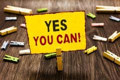 Handwriting text writing Yes You Can. Concept meaning Positivity Encouragement Persuade Dare Confidence Uphold Clothespin holding. Yellow paper note several stock image