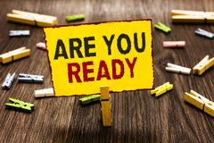 Handwriting text writing Are You Ready. Concept meaning Alertness Preparedness Urgency Game Start Hurry Wide awake Clothespin hold. Ing yellow paper note several royalty free stock images