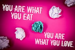 Handwriting text You Are What You Eat. You Are What You Love.. Concept meaning Start to eat healthy food Light pink floor circled. Shadow ruffled white paper royalty free stock photos
