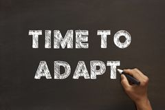 Time to Adapt. Handwriting Time to Adapt with chalk marker on blackboard royalty free stock photography