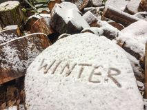 Handwriting of the word winter on a block of wood after first snow from close-up side angle.  stock images