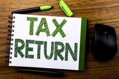 Handwriting zawiadomienia tekst pokazuje zwrot podatku Biznesowy pojęcie dla Podatkowego zwrota pisać na notatnika książkowym nut zdjęcia royalty free