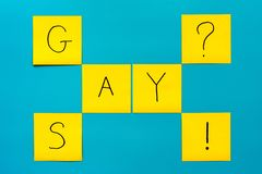 Handwritten black inscription gay and say on yellow square stickers on a blue background royalty free stock photo
