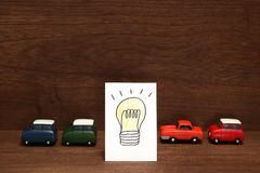 Handwritten bulb illustration and miniature cars on wood.  Royalty Free Stock Images