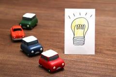Handwritten bulb illustration and miniature cars on wood.  Stock Image