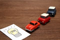 Handwritten bulb illustration and miniature cars on wood.  Royalty Free Stock Photography