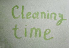 Handwritten cleaning time on dusty surface Stock Image