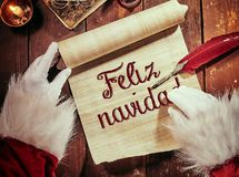 Handwritten Feliz Navidad or Merry Christmas. Greeting on a vintage scroll with the gloved hands of Santa Claus and a quill feather pen stock photo