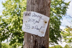 Handwritten French garage sale sign in Quebec. Charming paper sign on utility pole for garage sale Stock Photography