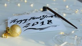Handwritten greeting Happy New Year 2018. Calligraphy inscription Happy New Year 2018. Lettering with black ink and broad nib pen illuminated with yellow stock video