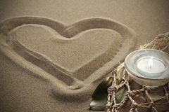 Handwritten heart on sand with lighted candles Royalty Free Stock Photo