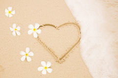 Handwritten heart on sand with wave approachin Stock Photos