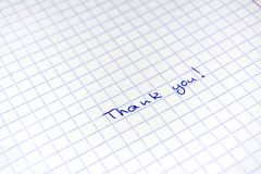 Handwritten inscription Thanks to the blue pen on a sheet in a cage royalty free stock photos