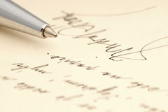 A handwritten message with a handwritten signature and a pen Royalty Free Stock Photo