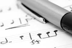 Handwritten notation. Handwritten musical notes lying with writing pen Stock Image