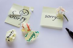 Handwritten note - I`m Sorry. Small delicate white flowers of al. Monds Stock Image