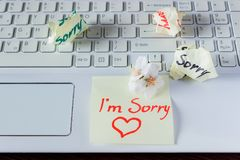 Handwritten note is on the keyboard. - I`m Sorry. Small delicate. White flowers of almonds stock photo