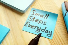 Handwritten quote Small steps everyday on table. Motivation concept stock photos