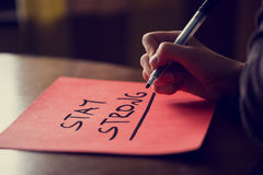 Handwritten Stay Strong Phrase on red Sticky Note Royalty Free Stock Images