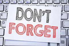 Handwritten text caption showing Do Not Forget. Business concept writing for Don t memory Remider written on sticky note paper on. White keyboard background Royalty Free Stock Image