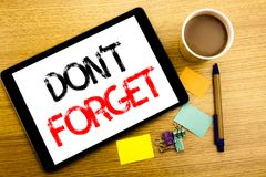 Handwritten text caption showing Do Not Forget. Business concept writing for Don t memory Remider Written on tablet laptop, wooden. Handwritten text caption Royalty Free Stock Photo