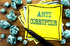 Handwritten text showing Anti Corruption. Business concept for Bribery Corrupt Text Written on sticky note paper, wooden backgroun. D marker folded yellow paper Royalty Free Stock Photos