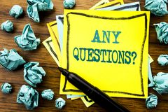Handwritten text showing Any Questions. Business concept for Answer Help Question Written on sticky note paper, wooden background. Marker folded yellow paper Stock Image