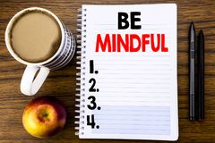 Handwritten text showing Be Mindful. Business concept for Mindfulness Healthy Spirit written on notepad note paper on the wood str. Handwritten text showing Be Stock Photos