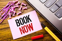 Handwritten text showing Book Now. Business concept for Reservation Buy Booking written on pink sticky note paper on the wooden ba. Handwritten text showing Book Stock Photography