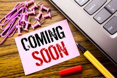 Handwritten text showing Coming Soon. Business concept for Message Future written on pink sticky note paper on the wooden backgrou Royalty Free Stock Photo