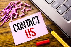Handwritten text showing Contact Us. Business concept for Customer Support written on pink sticky note paper on the wooden backgro. Handwritten text showing stock images