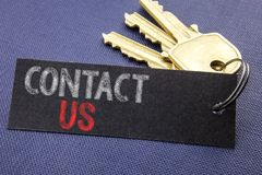 Handwritten text showing Contact Us. Business concept writing for Customer Support Written on note paper attached to the key, blac. Handwritten text showing stock image